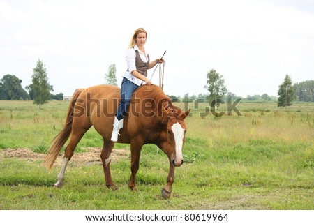 Beautiful blonde woman sitting on chestnut horse without saddle and bridle at the field