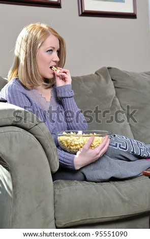 Beautiful blonde woman sitting on couch in pastel sweater and sweats eating from a bowl of popcorn and remote control - home entertainment - stock photo