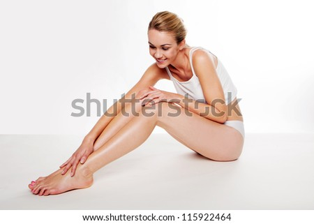 Beautiful blonde woman sitting on the floor caressing her smooth legs after waxing them - stock photo