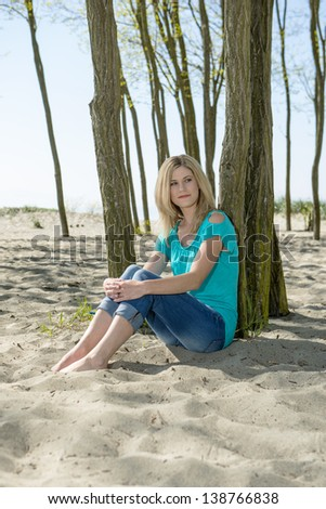 Beautiful blonde woman, sitting on the sand of a beach, with her back against a tree, with her arms wrapped around her knees - stock photo