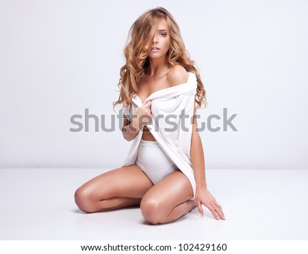 Beautiful blonde woman sitting on white background - stock photo
