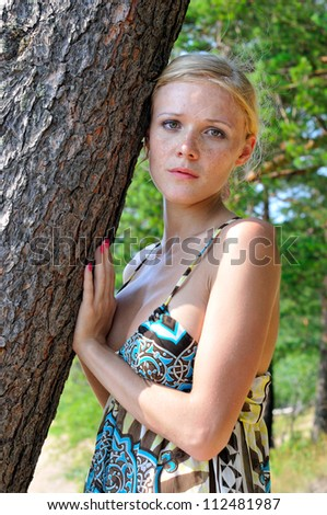 Beautiful blonde woman standing at the tree outdoors.