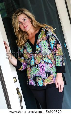 Beautiful Blonde Woman Standing in Doorway - stock photo