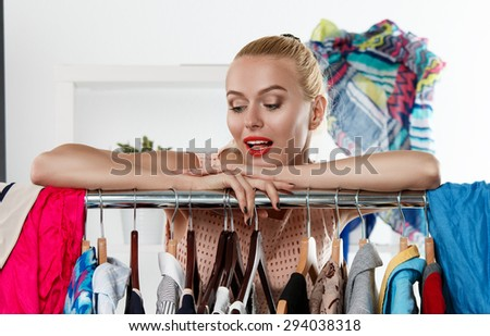 Beautiful blonde woman standing near wardrobe rack full of clothes and choosing dress. Shopping and consumerism or stylist concept. Nothing to wear and hard to decide concept