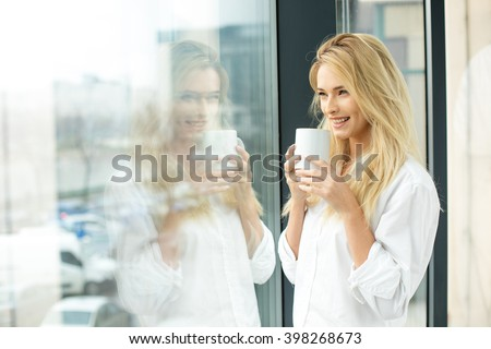 Beautiful blonde woman standing next to a window, wearing men shirt and drinking coffee