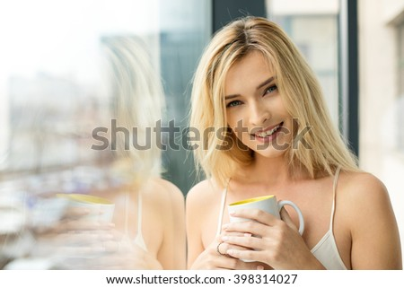 Beautiful blonde woman standing next to a window, wearing night clothes and drinking coffee