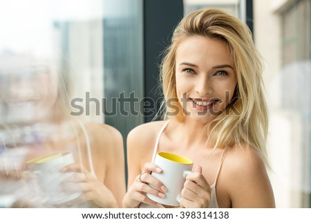 Beautiful blonde woman standing next to a window, wearing night clothes and drinking coffee - stock photo