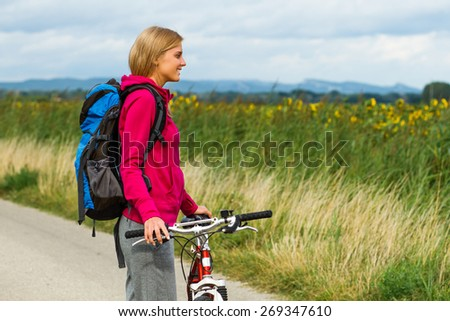 Beautiful blonde woman standing on the country road with her bike and enjoy in nature.Woman with a bike - stock photo