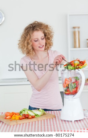 Beautiful blonde woman using a mixer in the kitchen in her apartment - stock photo