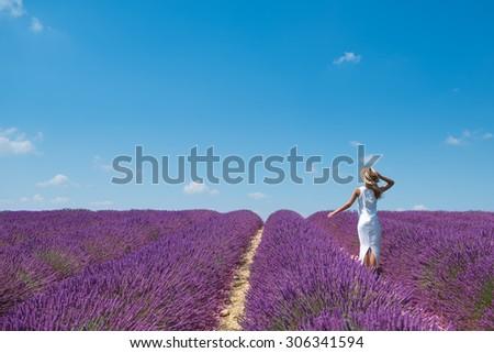 Beautiful blonde woman walking in lavender field  - stock photo