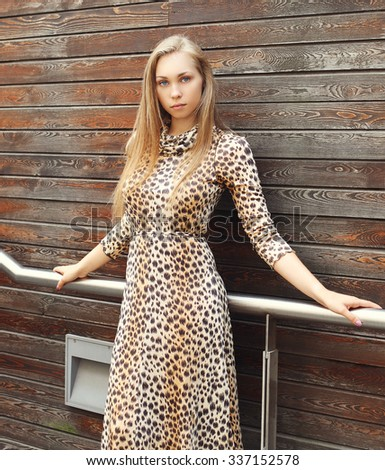 beautiful blonde woman wearing a leopard dress and sunglasses over wooden background - stock photo