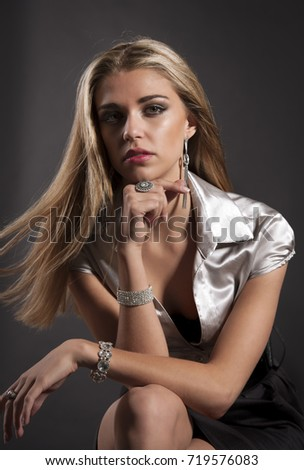 Beautiful blonde woman wearing a metallic shirt with earrings, ring and bracelet, posing with her arms on her knees in front of a black background