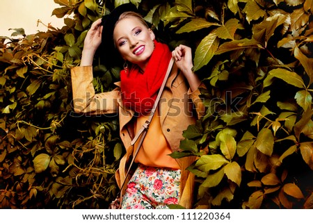 beautiful blonde woman wearing autumn clothes and a black hat against wall of leaves - stock photo