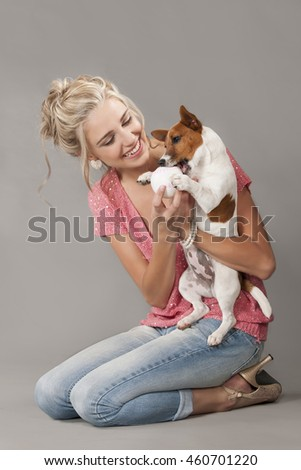 Beautiful blonde woman wearing jeans and pink sparkly top seated on the floor while playing with a small dog and a ball. - stock photo