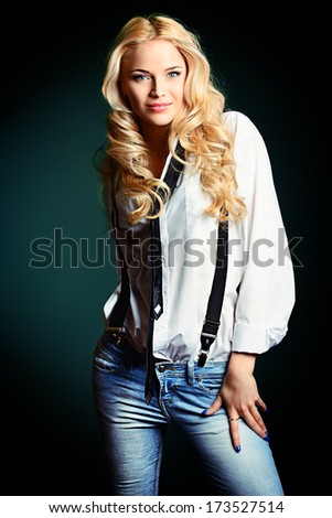 Beautiful blonde woman wearing white shirt and black tie posing over black background. - stock photo