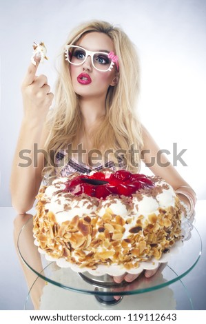 Beautiful blonde woman with a cake. Sweet sexy lady with glasses.