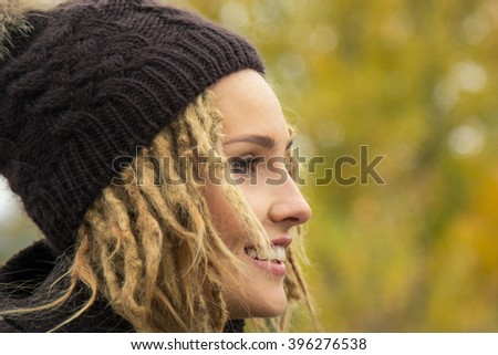 ... with a dreadlocks hairstyle in coat and knitted cap - stock photo