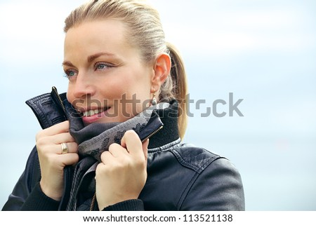 Beautiful blonde woman with a lovely radiant smile snuggling into the collar of her jacket against the cold weather