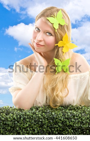 Beautiful blonde woman with butterfly decoration. - stock photo