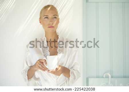 Beautiful blonde woman with cap of coffee or tea - stock photo
