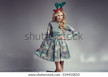 Beautiful blonde woman with christmas funny reindeer ears and nice dress. Happy expression. Christmas photo - stock photo