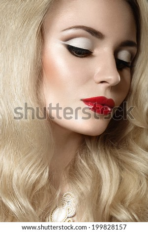 Beautiful blonde woman with evening make-up and red lips. Picture taken in the studio on a black background.