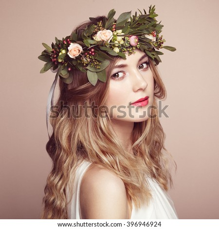 Beautiful blonde woman with flower wreath on her head. Beauty girl with flowers hairstyle. Perfect makeup. Beauty fashion. Spring woman - stock photo