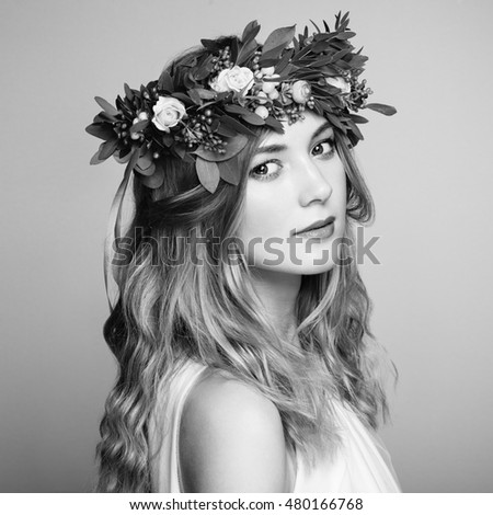 Beautiful blonde woman with flower wreath on her head. Beauty girl with flowers hairstyle. Perfect makeup. Beauty fashion. Spring woman. Black and White