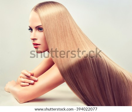 Beautiful blonde woman with long  straight  healthy and shiny hair.