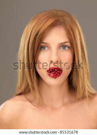 beautiful blonde woman with mouthfull of berries - stock photo