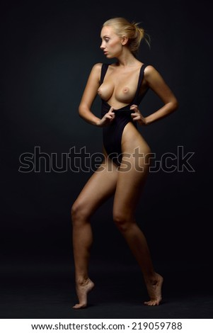 Beautiful blonde woman with naked breast in a black underwear posing in a dark Studio. - stock photo
