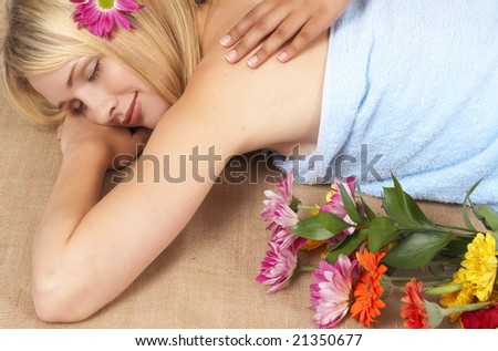 Beautiful blonde woman with natural make-up wrapped in towel receiving massage at a spa