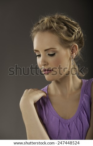 Beautiful blonde woman with natural makeup and braided hairstyle wearing a purple feminine shirt looking down and holding her hand to her shoulder - stock photo