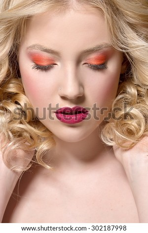 beautiful blonde woman with perfect curly hair. Woman with bright make up