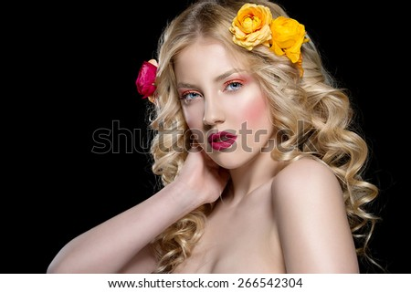 beautiful blonde woman with perfect curly hair. Woman with bright make up and flowers in her hair.  - stock photo