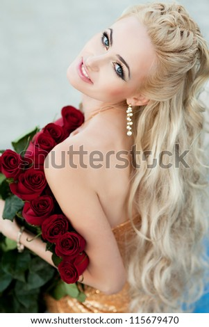 Beautiful blonde woman with red roses and long curly blond hair . Rich alluring girl in love dreaming and holding bouquet. lovely young lady with fresh flowers outdoor - stock photo