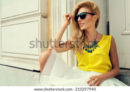 Beautiful blonde young woman holding sunglasses wearing fashionable clothes sitting on stairs - stock photo