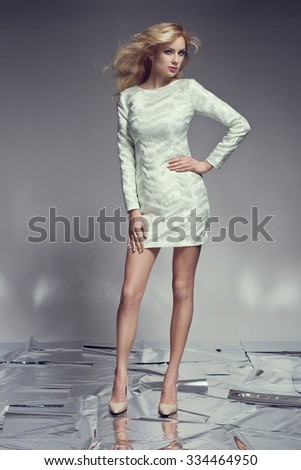 Beautiful blonde young woman in elegant evening black dress and high heels. Posing on shining mirror floor