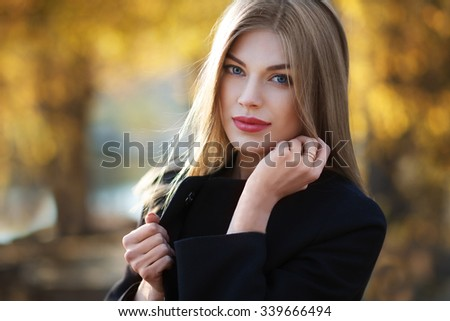 Beautiful blonde young woman in nice black coat. Posing on golden autumn background. Fashion Photo - stock photo