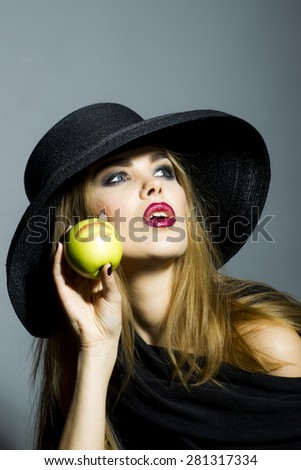 Beautiful blonde young woman in retro black hat with bright make up looking away holding fresh green apple standing on gray background copyspace, vertical picture - stock photo