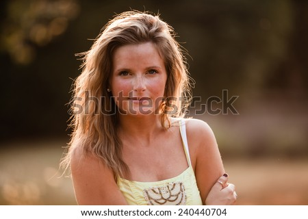 Beautiful Blonde Young Woman in sunset meadow summer day hand on arm slight smile