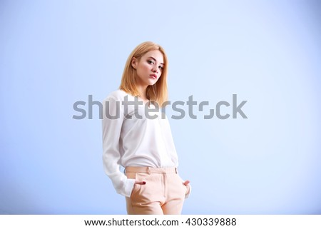 Beautiful blonde young woman in white shirt and beige pants on blue wall background - stock photo