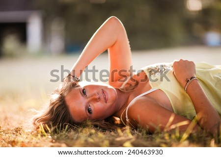 Beautiful Blonde Young Woman laying down in shade glowing skin variation hand on head - stock photo