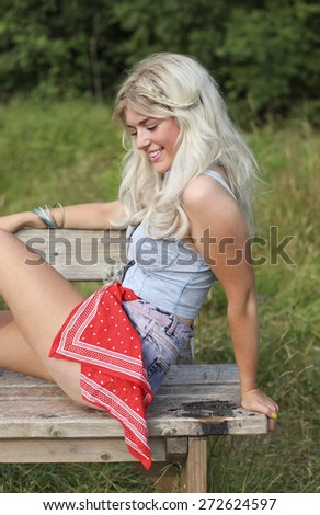 Beautiful blonde young woman sitting on a wooden bench outdoors