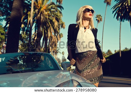 Beautiful blonde young woman wearing fashionable clothes, black cardigan posing next to a car on the street with palm trees. Fashion photo - stock photo