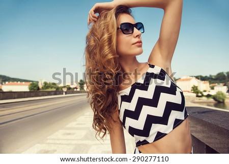 Beautiful blonde young woman wearing fashionable clothes, handbag, sunglasses posing in the city. Fashion photo - stock photo