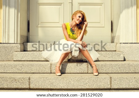 Beautiful blonde young woman wearing fashionable clothes sitting on stairs - stock photo