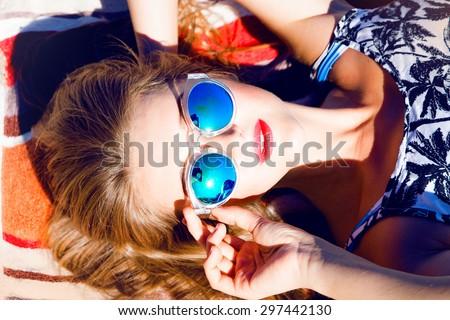 Beautiful blonde young woman wearing sunglasses,shorts,green top and handbag, laying on the beach,red lips,fresh face,model face,tan woman,sensual woman,long hair,reflection sunglasses,mirrored glass - stock photo
