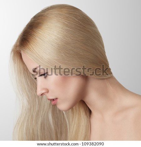 Beautiful blonde young woman with long hair studio portrait - stock photo