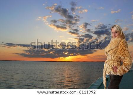 Beautiful blondie standing on the beach in sunrise lights - stock photo